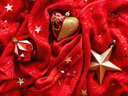 Bright red fabric with Christmas and New Year decorations - golden star, heart and ball. Star confetti on folded textile background. 写真素材