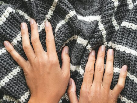 Womans hands on gray knitted sweater with white stripes. Folded warm clothing. Crumpled textile background.