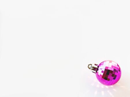 New Year background with magenta ball. Pink reflections, sunbeams on white copy space with decorative ball for Christmas tree.