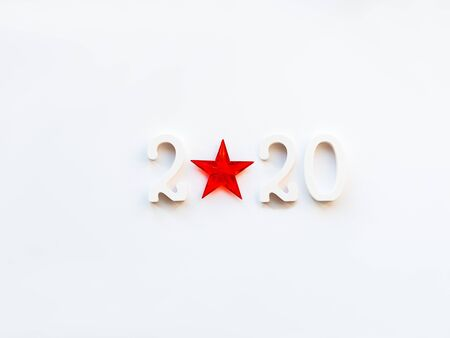 New Year 2020 background with bright red star. Numbers 2020 on white copy space with decorative ball for Christmas tree.