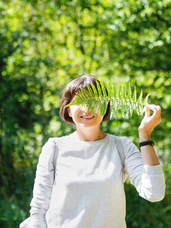Young woman is hiding her eyes with fern leaf.  Symbol of life, tranquility and unity with nature. Summer in forest.