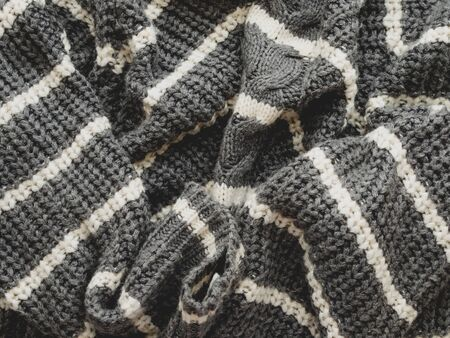 Gray knitted sweater with white stripes. Folded warm clothing. Crumpled textile background. 写真素材