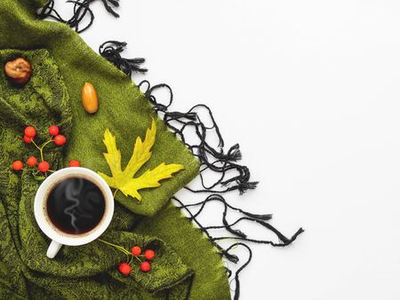 Green scarf with fallen leaves and berries on white background. White cup of hot coffee on folded warm accessory with copy space.