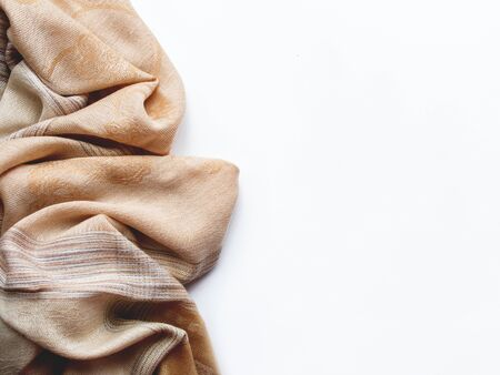 Beige and brown scarf on white background. Folded warm accessory with copy space.