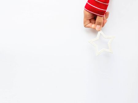 Woman in red sweater is holding New Year decoration - white star on white background. Top view on decoration for Christmas tree. 写真素材