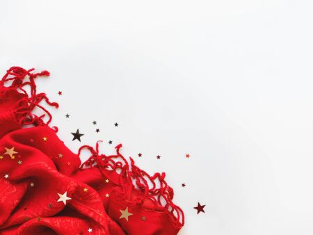 Bright red scarf with silver and golden stars confetti on white background. Folded warm accessory with copy space. 写真素材