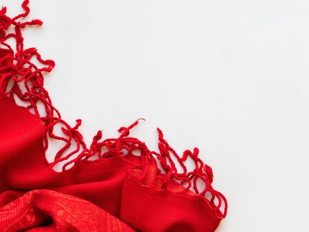 Bright red scarf on white background. Folded warm accessory with copy space.