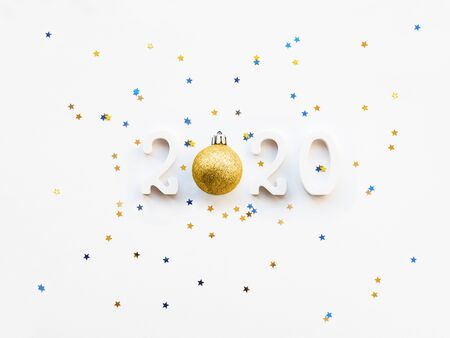 New Year 2020 background with golden ball and star confetti. Numbers 2020 on white copy space with decorative ball for Christmas tree.