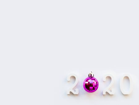 New Year 2020 background with purple ball. Numbers 2020 on white copy space with decorative ball for Christmas tree. 写真素材