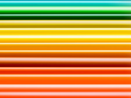 Horizontal row of orange, yellow and green watercolor pencils. School supplies background. Kids stationery. Back to school backdrop with abstract rainbowgradient lines.