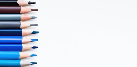 Row of colorful blue and brown pencils on white background. School supplies on blackboard. Kids stationery. Back to school copy space backdrop.