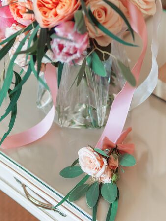 Bridal bouquet with pink and coral roses. Grooms boutonniere with similar flowers. Traditional accessories for wedding.