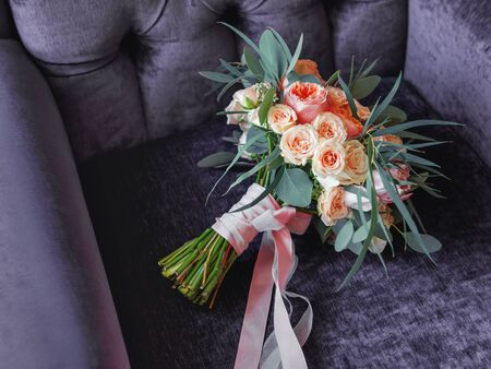 Wedding bouquet on chair. Brides traditional symbolic accessory. Floral composition with peonies and roses.
