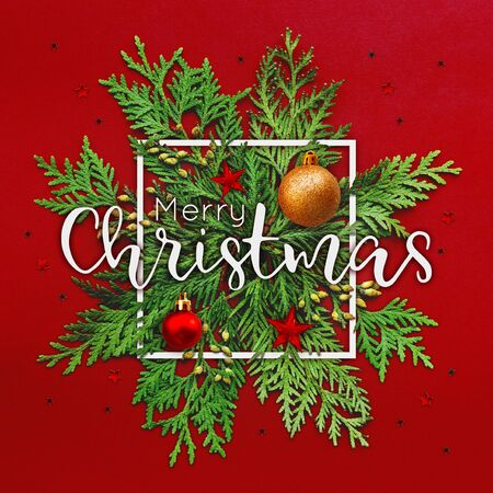 Christmas background with thuja branches and words MERRY CHRISTMAS in white square frame. Trendy Xmas greeting  with stars and ball decorations on red backdrop. Stock fotó