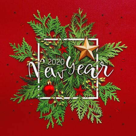 Christmas background with thuja branches and words NEW YEAR 2020 in white square frame. Trendy Xmas greeting  with stars and ball decorations on red backdrop.