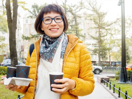 Happy wide smiling women in bright yellow jacketis holding paper cup with hot coffee. Hot beverage on cool autumn day.