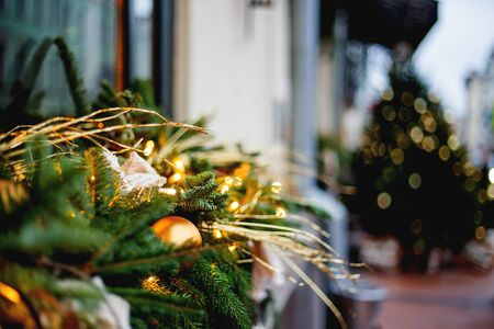 Christmas and New Year outdoor decorations -  traditional fir tree wreaths with light bulbs, pine cones and balls.