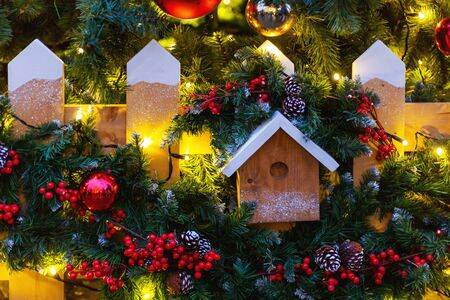 Christmas and New Year outdoor decorations - bird house with traditional fir tree wreaths.