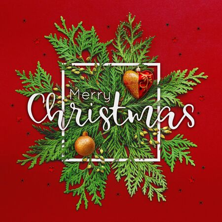 Christmas background with thuja branches and words MERRY CHRISTMAS in white square frame. Trendy Xmas greeting  with stars and heart decorations on red backdrop. Stock fotó