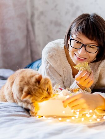 Cute ginger cat with bites light bulbs. Woman playing with her fluffy pet and box with Christmas decorations. Cozy home before New Year.