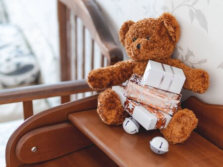 Teddy bear in kids room before New Year.. Plush toy with Christmas presents wrapped in white and golden paper.