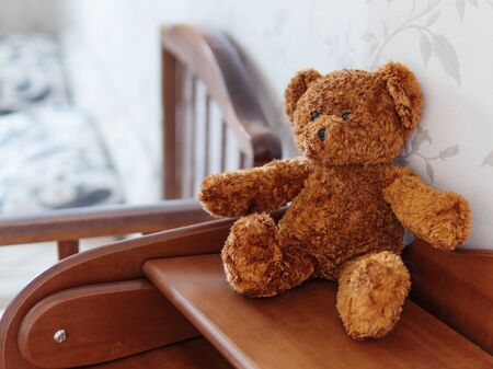 Teddy bear on wooden dresser. Plush toy in kids room.