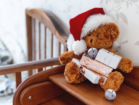 Teddy bear in Santa Claus hat. Plush toy with Christmas presents wrapped in white and golden paper. Kids room before New Year. Stock Photo