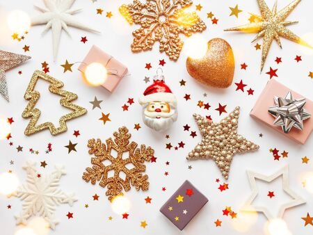 Christmas and New Year background with sparkling fir tree, Santa Claus, heart, snowflakes and star confetti. Holiday decorations on white background with light bulbs.