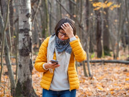 Woman in bright yellow jacket watching on her smartphone with puzzled expression. Maybe she got lost in autumn forest or battery of her gadget got low.