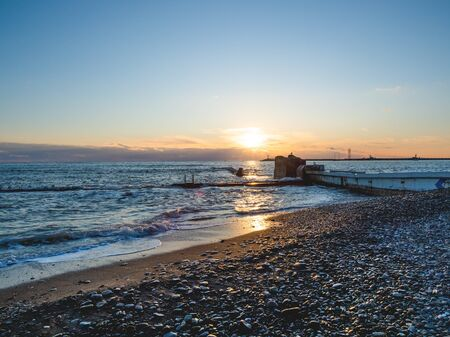 Beautiful sunset over Black sea in Sochi, Russia. Silhouettes of seagulls on rocks and tranquil sea surf.
