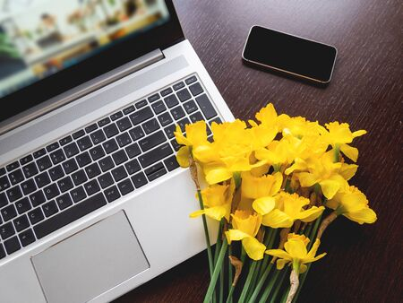 Bouquet of Narcissus or daffodils lying on silver metal laptop. Bright yellow flowers on portable device. Smartphone on wooden background.