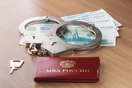 Locked handcuffs, certificate of employee of the Ministry of internal Affairs and Russian banknotes. Legal responsibility and monetary fine for violating isolation during coronavirus COVID-19 quarantine.