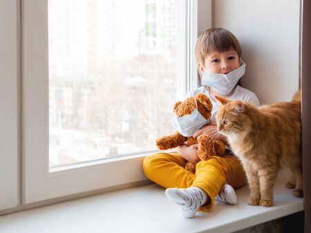 Toddler boy sits with teddy bear, both in medical masks. Kid with cute ginger cat. Fluffy pet and child on home quarantine because of coronavirus COVID-19.