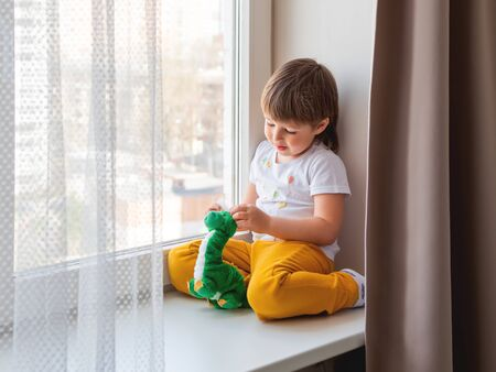 Toddler boy sits with green dragon or dinosaur. Kid with plush toy look through window outside. Child on home quarantine because of coronavirus COVID-19 waiting for somebody. 版權商用圖片