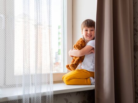 Toddler boy sits with teddy bear. Kid with plush toy plays hide-and-seek and hides behind curtain. Brown bear and child on home quarantine because of coronavirus COVID-19. Foto de archivo
