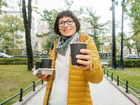 Take away coffee. Happy wide smiling women in bright yellow jacket holds paper cup with freshly brewed cappuccino. Hot beverage on cool autumn day.