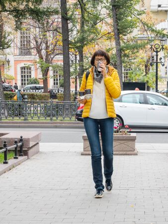 Take away coffee. Women in bright yellow jacket holds paper cup with freshly brewed cappuccino. Hot beverage on cool autumn day.
