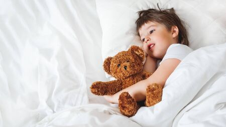 Toddler lies in bed with cute teddy bear. Little boy under white blanket with fluffy toy. Plush guard watches out child's sleep. Background with copy space.
