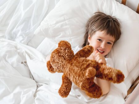 Toddler lies in bed with cute teddy bear. Little boy under white blanket with fluffy toy. Plush guard watches out child's sleep. Morning bedtime at cozy home. Banque d'images