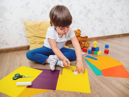 Toddler boy learns to cut colored paper with scissors. Kid sits on floor in kids room with toy blocks and teddy bear. Educational classes for children. Developing feeling sensations and fine motor skills at home.