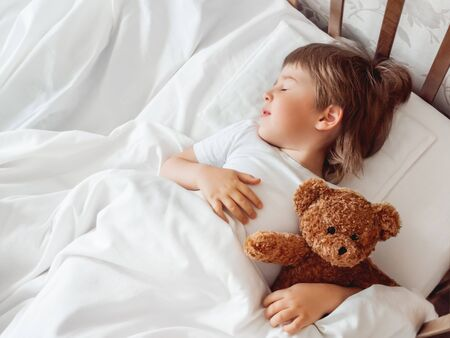 Toddler sleeps in bed with cute teddy bear. Little boy under white blanket with fluffy toy. Plush guard watches out child's sleep. Cozy home. Banque d'images