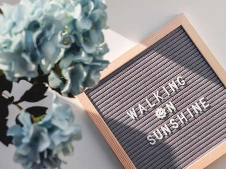 Top view on letter board with word Walking on Sunshine. Flat lay concept symbol of warmth and light. 免版税图像