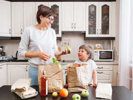 Woman and toddler boy sorts out purchases in the kitchen. Kid bites an apple. Grocery delivery in paper bags. Subscription service from grocery store. Mother and son at kitchen.