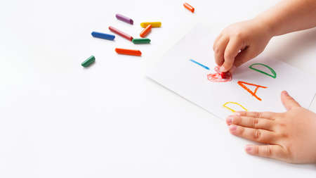 Toddler draws greeting card for Father's day. Kid uses wax crayons to write I Love Dad and to paint red heart symbol. Child's hands and pencils on white background with copy space.