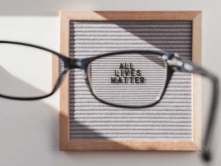 Top view on letter board with words All Lives Matter through eyeglasses. Flat lay concept with actual statement. Social issue. Race problem in society.