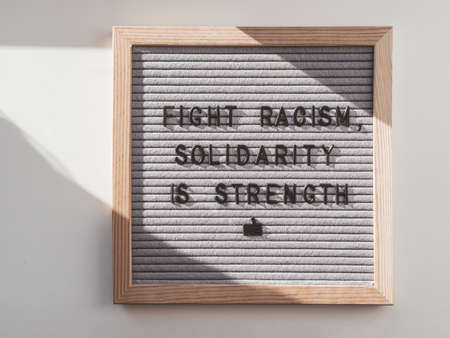 Top view on letter board with words Fight Racism, Solidarity is Strength. Flat lay concept with actual statement. Social issue. Race problem in society.