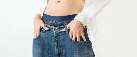 Woman hides her palm with engagement ring in pocket of classic blue jeans. Modern fashion - low rise boyfriend jeans and white shirt.