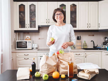 Woman sorts out purchases in the kitchen. Grocery delivery in paper bags. Subscription service from grocery store in conditions of quarantine because of coronavirus COVID19.