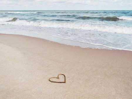 Sea coast with soft surf. Heart drawn on sandy beach. International symbol of love and romance. Vacation on seaside.