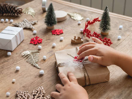 Kid wrapped Christmas presents in craft paper with white fluffy pompons and fringe as decoration. Wooden table with hand made New Year gifts.